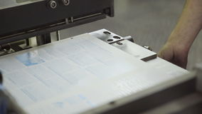 Master bookbinder puts sheet of newspaper on equipment for press stock video footage