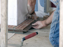 Master Bricklayer Ensures Quality. Master bricklayer uses square to ensure quality royalty free stock images