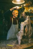 Master carpenter 50 - 55 years old creates wooden sculpture. In the workshop stock photography