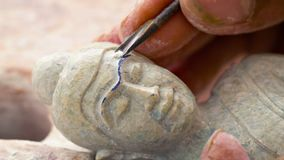 Master carves a sculpture of Buddha. Stone-cutting workshop in Cambodia stock footage