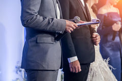 Master of ceremonies with microphone. On stage Royalty Free Stock Images