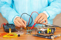 Master checks board of electronic device with a multimeter Royalty Free Stock Images