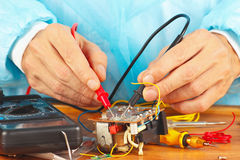 Master checks the electronic components of device with multimeter Stock Photos