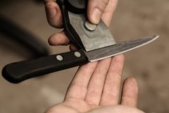 The master checks the sharpening of a knife from Damascus steel stock photography