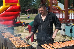Master chef barbecue. Photograph of a person cooking on a BBQ grill with the flames showing. Chef at dinner buffet barbecue, focused on grill. Chef preparing Stock Photo