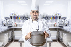 Master chef and pot. Smiling chef holding a saucepan standing on a kitchen background royalty free stock photos