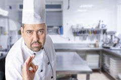 The master chef showing ok sign. Portrait of the master chef showing ok sign standing on a kitchen background - focus on the face Royalty Free Stock Images