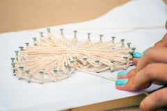 Master class in the park. How to make a picture of threads. And nails stock image