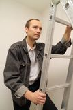 Master climbs a ladder up. Repair Indoor. Master climbs a ladder up Royalty Free Stock Photography