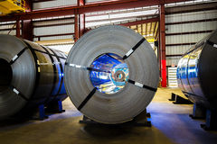 3 master coils in warehouse with coil seen inside eye of coil an Royalty Free Stock Photography