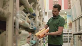 Master is comparing two kind of wallpaper in a shop, shopping for repairs. Designer man is choosing wallcovering in a building store. He is holding two rolls of stock video