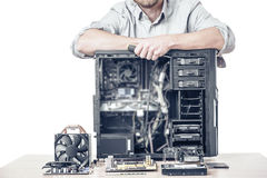 Master of computer repair. Computer repair concept. Master of computer repair put his hands on the disassembled computer system unit. Toned photo Stock Images