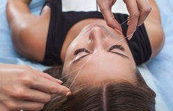 Master corrects makeup, gives shape and thread plucks eyebrows in a beauty salon. Stock Image