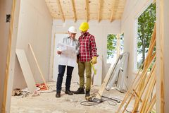Master craftsman and artisan working. And planning new building royalty free stock photography