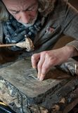 Silversmith at work on a silver plate. Master craftsman engraves a silver plate with hammer and chisel stock images