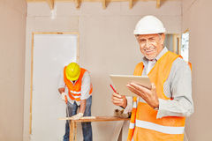 Master craftsman with tablet Stock Images