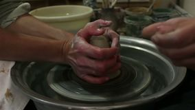 The master creates a white clay product. The master`s hands close-up sculpt a clay product using a potter s wheel. The