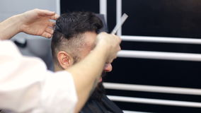 Master cuts hair and beard of man in a barbershop. stock video footage
