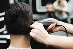 Master cuts hair and beard of men in the barbershop, hairdresser. Master cuts hair and beard of man in the barbershop, hairdresser makes hairstyle for a young stock images