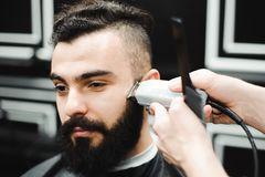 Master cuts hair and beard of men in the barbershop, hairdresser. Master cuts hair and beard of man in the barbershop, hairdresser makes hairstyle for a young stock photos
