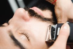 Master cuts hair and beard of men in the barbershop, hairdresser. Master cuts hair and beard of man in the barbershop, hairdresser makes hairstyle for a young royalty free stock images