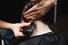 Master cuts hair and beard of men in the barbershop, hairdresser. Master cuts hair and beard of man in the barbershop, hairdresser makes hairstyle for a young royalty free stock image