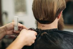 Master cuts hair and beard of men in the barbershop, hairdresser makes hairstyle for a young man stock images