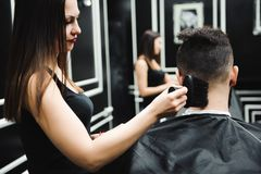 Master cuts hair and beard of men in the barbershop, hairdresser. Makes hairstyle for a young man royalty free stock photo