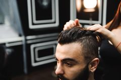 Master cuts hair and beard of men in the barbershop, hairdresser makes hairstyle for a young man. royalty free stock image