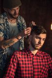 Master cuts hair and beard of men Royalty Free Stock Images