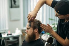 Master cuts hair and beard of men in the barbershop, hairdresser makes hairstyle for a young man.  stock images