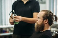 Master cuts hair and beard of men in the barbershop, hairdresser makes hairstyle for a young man royalty free stock photos