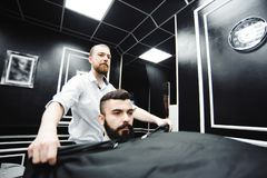 Master cuts hair and beard of men in the barbershop, hairdresser. Makes hairstyle for a young man stock image