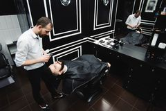 Master cuts hair and beard of men in the barbershop, hairdresser. Makes hairstyle for a young man stock photo