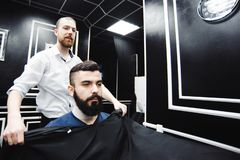 Master cuts hair and beard of men in the barbershop, hairdresser. Makes hairstyle for a young man royalty free stock images
