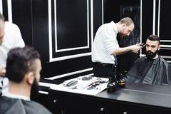 Master cuts hair and beard of men in the barbershop, hairdresser. Makes hairstyle for a young man stock photos