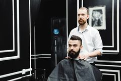 Master cuts hair and beard of men in the barbershop, hairdresser. Makes hairstyle for a young man stock images