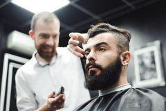 Master cuts hair and beard of men in the barbershop, hairdresser. Makes hairstyle for a young man royalty free stock photos