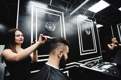 Master cuts hair and beard of men in the barbershop, hairdresser. Makes hairstyle for a young man royalty free stock photography