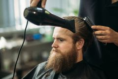 Master cuts hair and beard of men in the barbershop and uses a hair dryer royalty free stock photo
