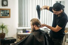 Master cuts hair and beard of men in the barbershop and uses a hair dryer stock images