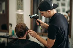 Master cuts hair and beard of men in the barbershop and uses a hair dryer royalty free stock images