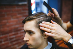 Master cuts hair of men in the barbershop Royalty Free Stock Photo