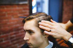 Master cuts hair of men in the barbershop Stock Image