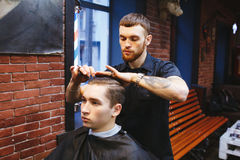 Master cuts hair of men in the barbershop Royalty Free Stock Photography