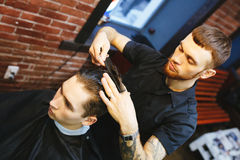 Master cuts hair of men in the barbershop Stock Photography