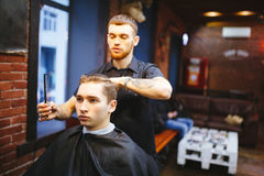 Master cuts hair of men in the barbershop Stock Images