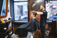 Master cuts hair of men in the barbershop Royalty Free Stock Photos