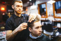 Master cuts hair of men in the barbershop Royalty Free Stock Image