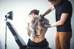 Tattoo tiger on the back. The master does a tattoo on the back. Two men on a white background. Tattoo tiger royalty free stock image